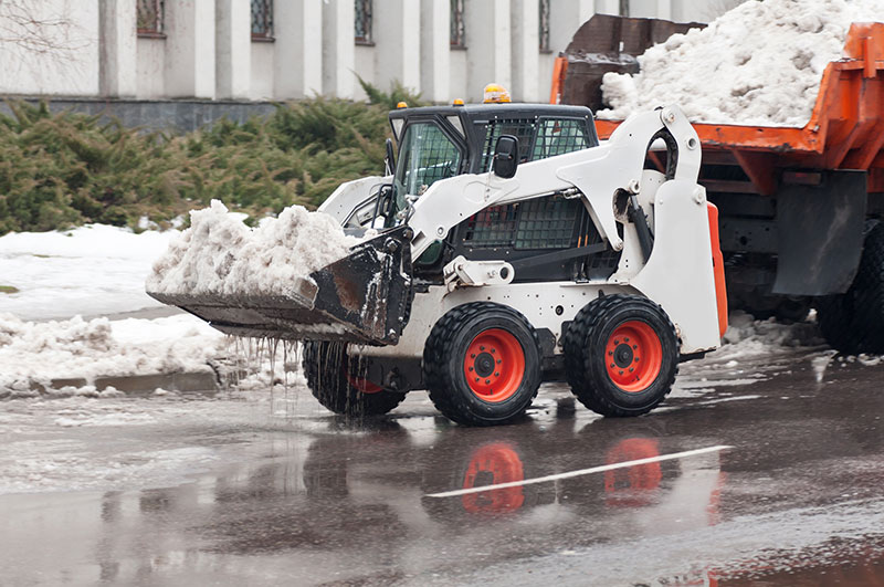 Snow removal on the street using skid steer loader